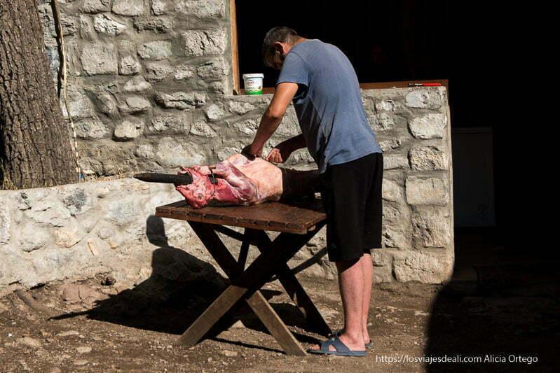hombre preparando una cabra ya ensartada en un palo para asarla en el fuego