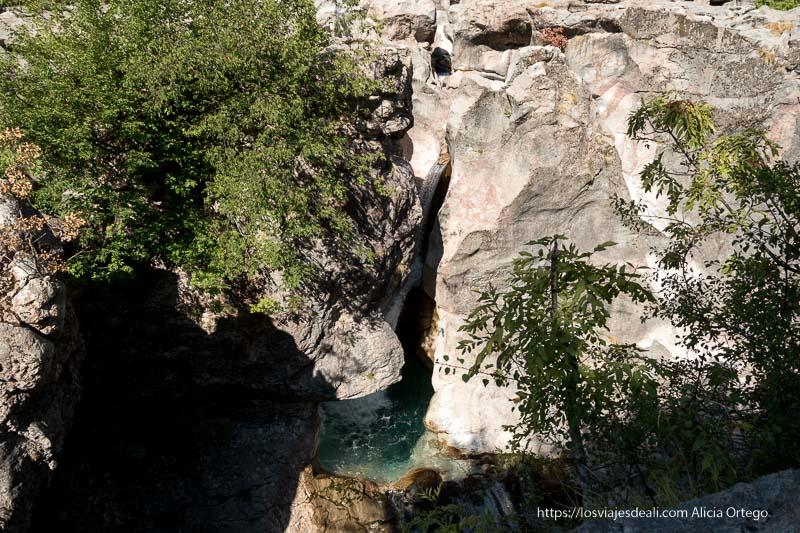 cascada semiescondida entre rocas pulidas por la acción del agua