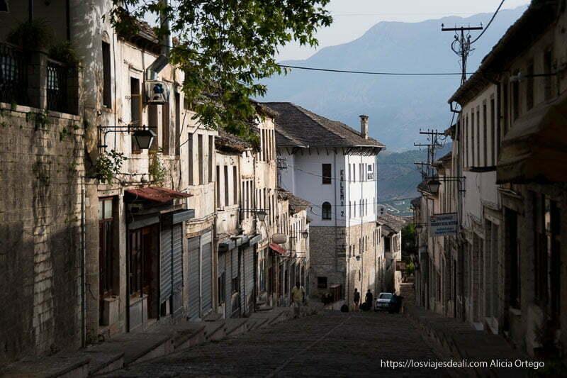 calle empedrada con casas antiguas y montaña al fondo en el viaje a albania en 12 días