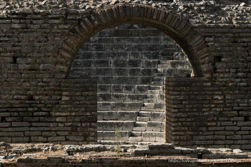 arco de piedra a través del que se ven las gradas y escaleras del teatro