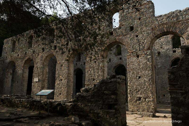 ruinas de basílica con dos paredes con 6 arcos altos en piedra y ladrillo