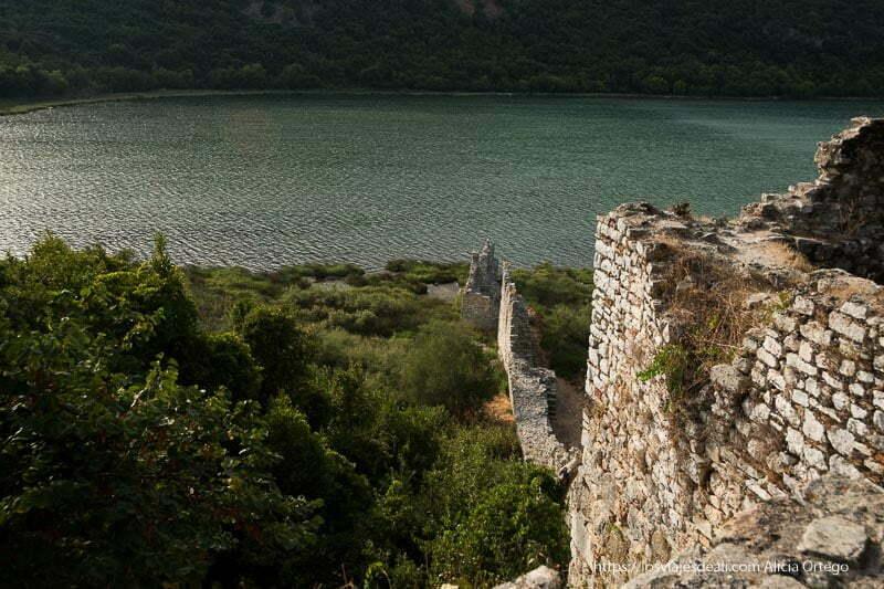 vista del lago con murallas de las ruinas de butrinto bajando casi hasta el agua
