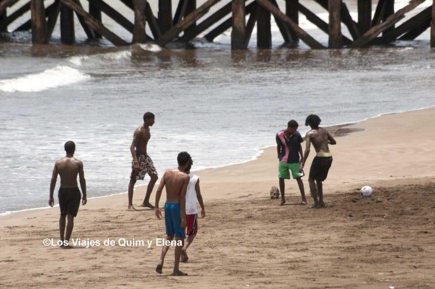 Chicos jugando en la playa en Praia