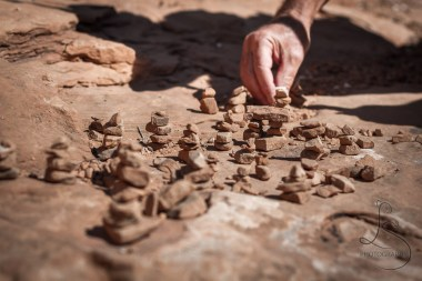 A man carefully arranges a new tiny cairn to the existing garden.