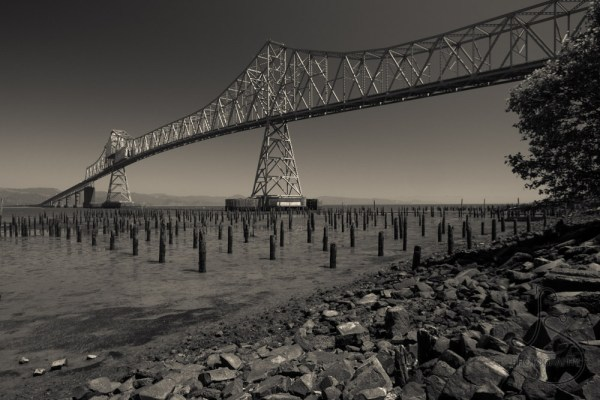 Monochrome rendition of the Astoria Bridge from below on the rocky river shoreline with old wooden pylons
