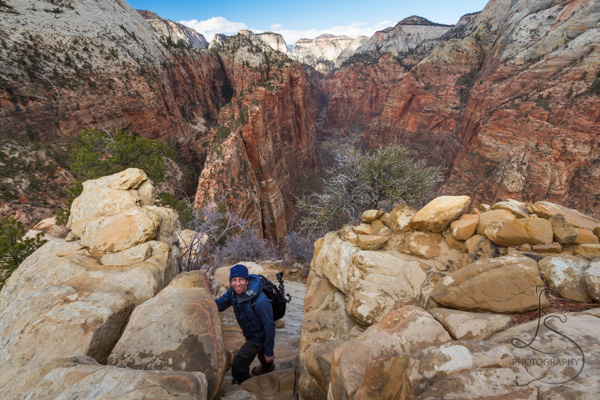A man just reaching the top of the Angels Landing hike in Zion National Park, with the valley far below behind him | LotsaSmiles Photography
