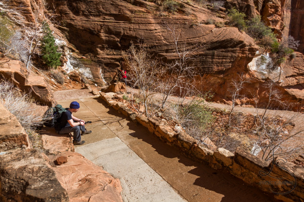 Hikers resting along the side of the Angels Landing hike in the hot sun | LotsaSmiles Photography
