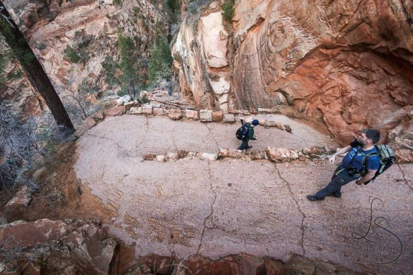 Two people descending Walter's Wiggles on the Angels Landing trail, viewed from above | LotsaSmiles Photography