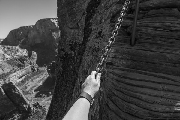 A hand gripping a chain in the rock face, with nothing but the Zion valley floor 2000 feet below the Angels Landing summit   LotsaSmiles Photography