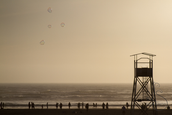 Giant bubbles floating over silhouettes of people and a lifeguard riser on the beach at Seaside at sunset