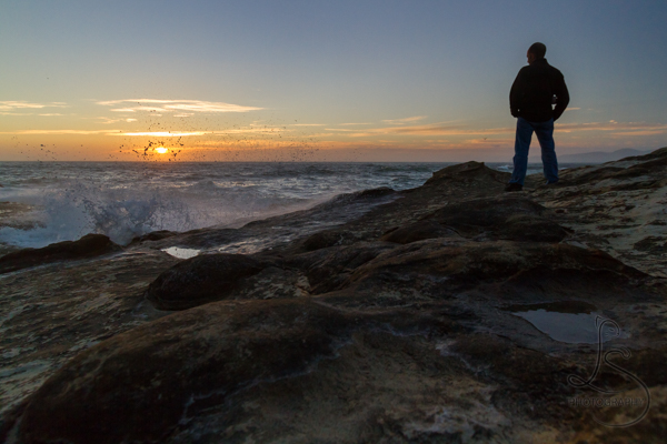 A man stands silhouetted on a rocky shore in front of the last rays of sunset | LotsaSmiles Photography