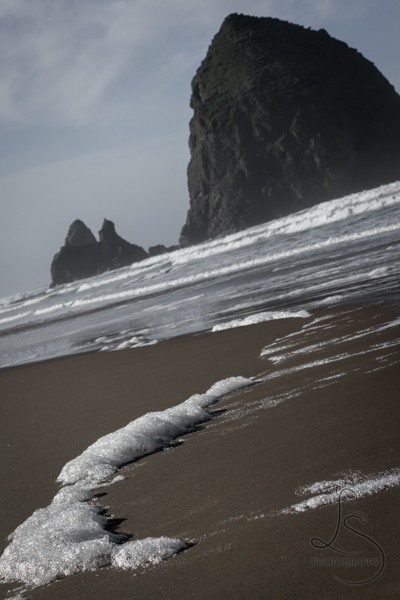 Sea foam on the beach in front of Haystack Rock in Cannon Beach | LotsaSmiles Photography