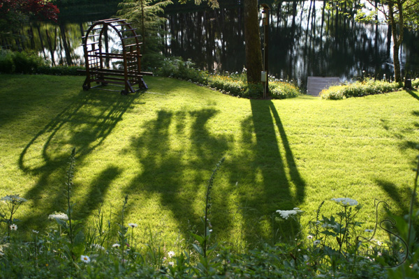 An altar on a grassy lake bank, with evening shadows stretching toward the viewer (unedited) | LotsaSmiles Photography