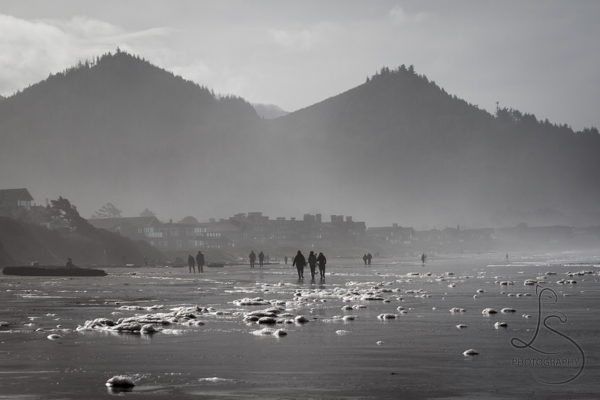 Silhouette of people on a foamy beach, with hazy mountains in the background | LotsaSmiles Photography