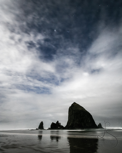 Stars peeking through the cloud cover above Haystack Rock in Cannon Beach | LotsaSmiles Photography