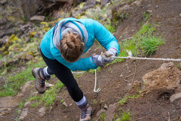Woman scrambling down a steep incline with the aid of a rope | LotsaSmiles Photography