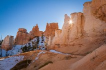 The sun peeks through the hoodoos as it sets over a frozen Bryce National Park