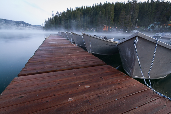 Boats tied at a frozen dock on a misty morning lake | LotsaSmiles Photography