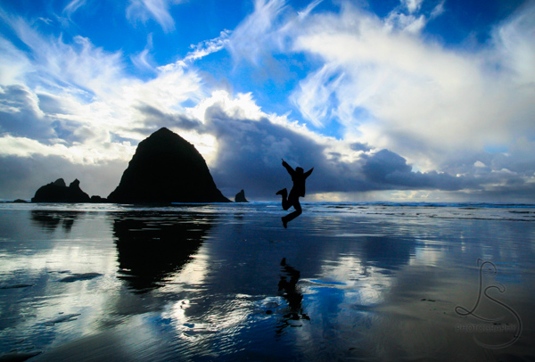 Aaron jumping in front of Cannon Beach's Haystack Rock at sunset | LotsaSmiles Photography