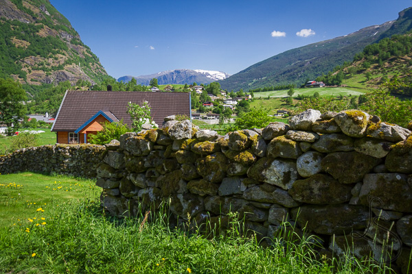 Rock wall in front of a quaint house in a green Norwegian valley | LotsaSmiles Photography