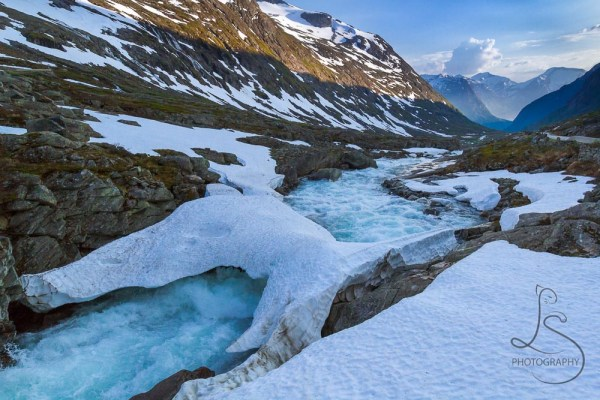 A thick layer of ice bridges a chilly stream in Norway.