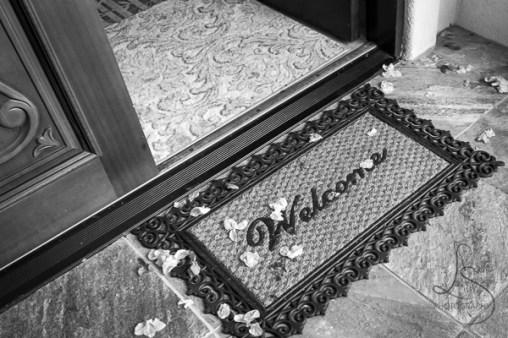 A warm Hawaiian welcome, complete with welcome mat, open door, and flower petals