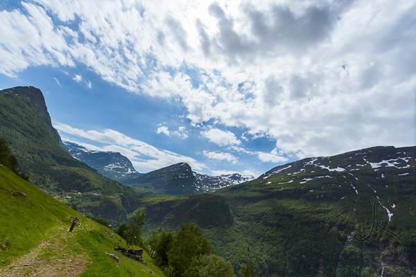 Aaron crossing the field on the Losta trail, with the Norwegian landscape beyond | LotsaSmiles Photography