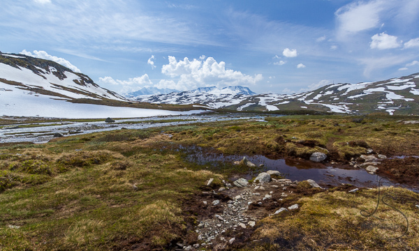 Blood-red pond in front of snowy mountains | LotsaSmiles Photography