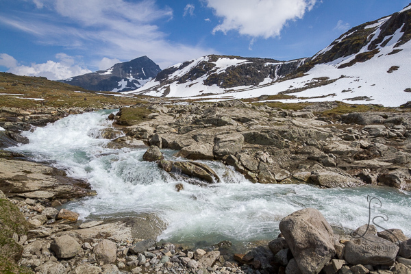 A glacial creek in the foreground and a snowy mountain range behind | LotsaSmiles Photography