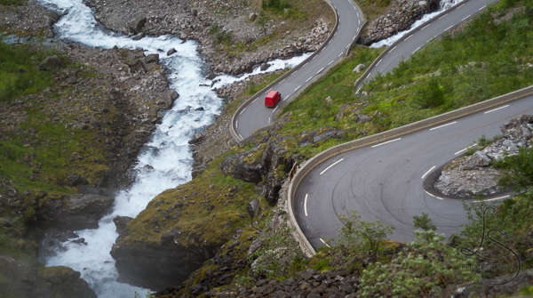 A red van driving down the famous zigzag road of Trollstigen in Norway | LotsaSmiles Photography