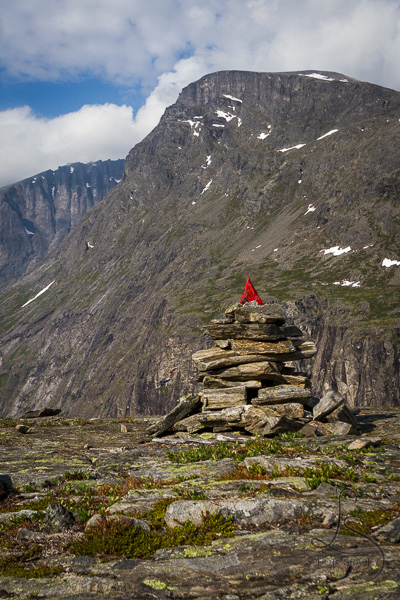 A cairn topped with a red-painted rock along the trail above the Trollstigen viewpoint in Norway | LotsaSmiles Photography