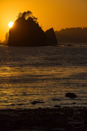 The sun sets behind a sea rock in Olympic National Park