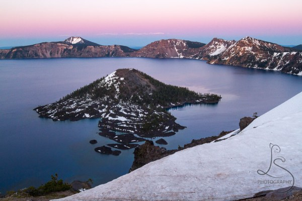 Crater Lake's Wizard Island stands still at dusk.