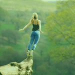 What does your brand stand for picture of a woman standing on a branch over a valley with her arms back