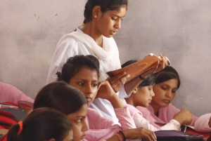 Girl At School Reading to Class: Lotus Outreach International