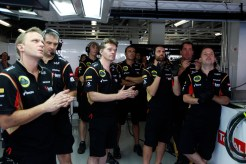 The Lotus F1 team applaud their drivers efforts in the garage.