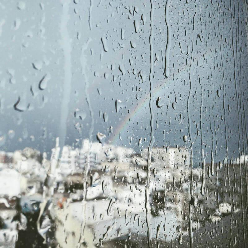 rainbow outside a raining window