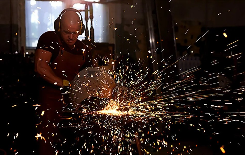 machinist grinding metal and creating sparks for industrial profile videos for the fastener industry