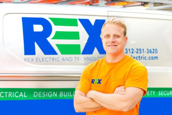 Portfolio image of a Rex Electric employee smiling in front of his van for a photography shoot of team employees