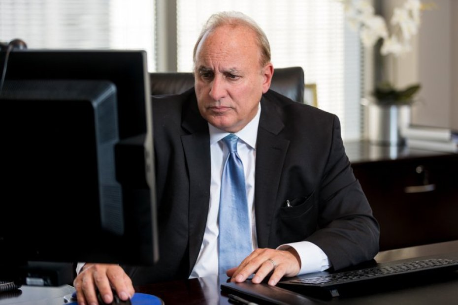 a businessman seated at his desk working on the computer as photographed for photography campaign by Loudbyte