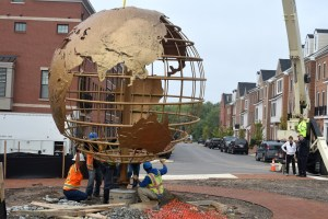 The former Leisure World globe sculpture is lowered into place at its new home in Crescent Place.