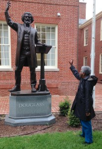 In one of her favorite photographs, Elaine E. Thompson salutes the statue of one of her heroes, social reformer Frederick Douglass, at the courthouse in Easton, MD. [Deborah Lee]