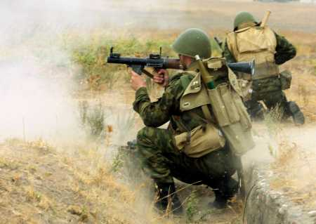 A Russian soldier fires an RPG to enemy position in an unknown location.