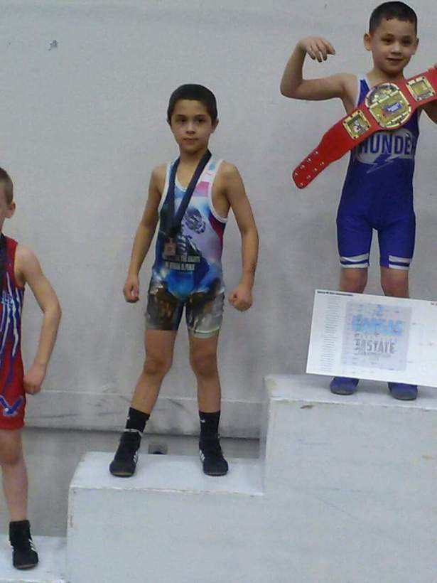 Noah Caudill stands on the medal stand after finishing third place at 58 pounds at the 6-and-under kids state wrestling tournament Sunday in Salina.