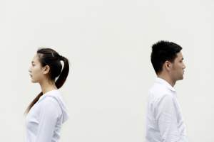 Woman and man stood apart with their backs to each other against a white background.