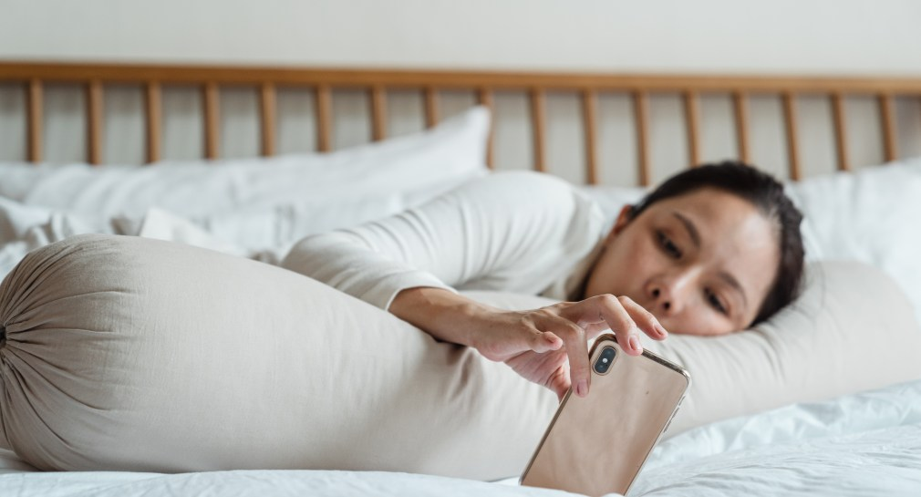 Lady procrastinating on bed with phone