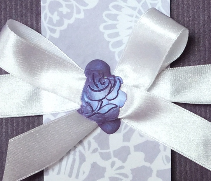 A white bow held in place by a lilac wax seal