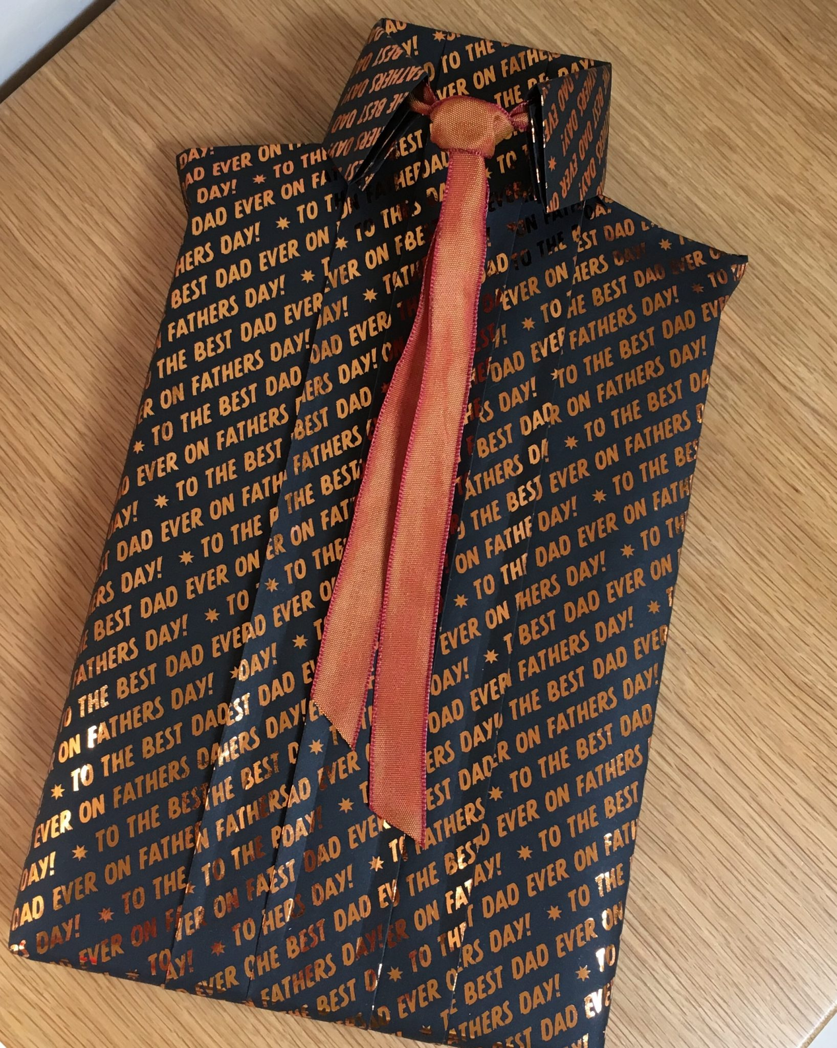 A book wrapped to look like a shirt using black giftwrap & a copper tie
