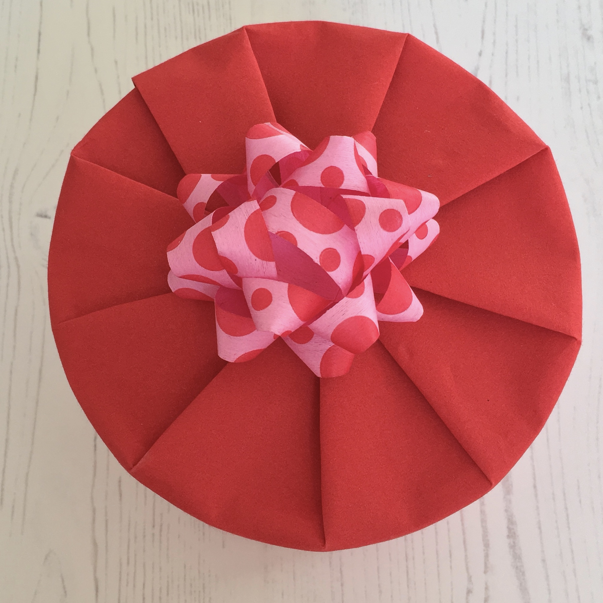 A circular item wrapped in red giftwrap, with a pleated effect and a pink/red paper bow on top
