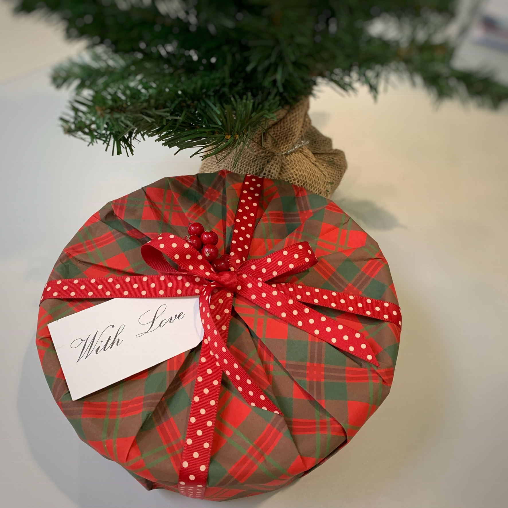 A sweet tin covered in red & green tartan giftwrap with a red and white spotty ribbon